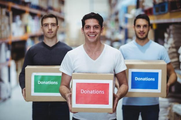 Freiwillige, die an der kamera hält spendenkästen in einem großen lager lächeln