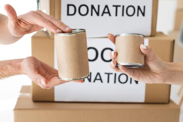 Freiwillige, die dosen für spendenboxen halten