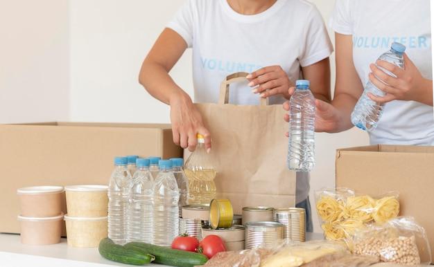 Freiwillige, die essen und wasser zur spende in die tasche stecken