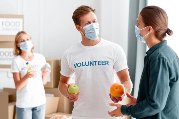 Freiwillige, die helfen und lebensmittel für spenden verpacken