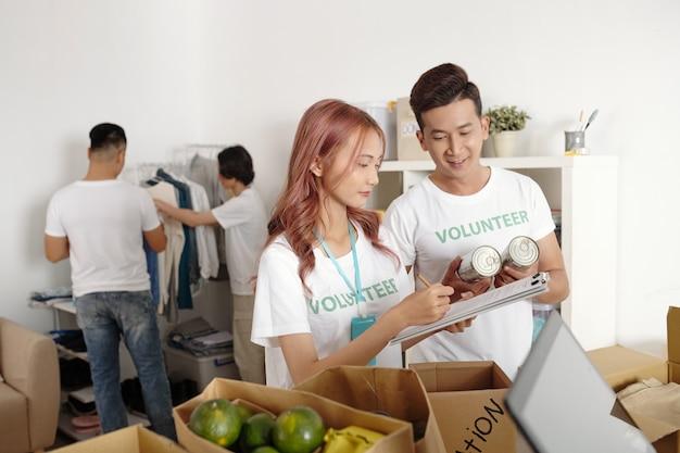 Freiwillige, die in einer gemeinnützigen stiftung arbeiten, machen notizen in einem dokument und beschreiben alle lebensmittel und kleidung, die sie für bedürftige menschen einpacken