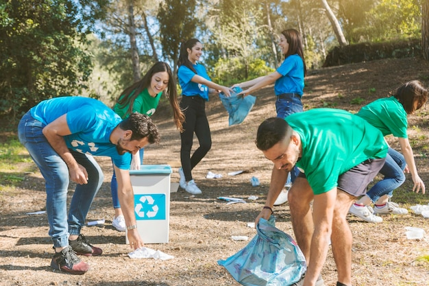 Freiwillige, die in netten wäldern aufräumen