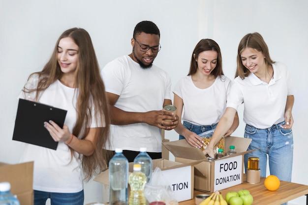 Freiwillige, die kisten für die spende mit lebensmitteln vorbereiten