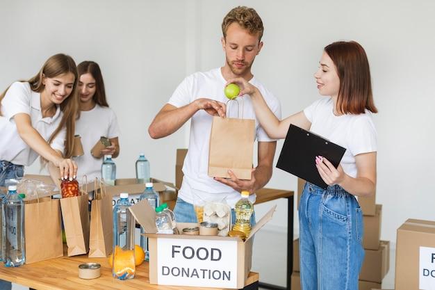 Freiwillige, die kisten mit lebensmitteln für die spende vorbereiten