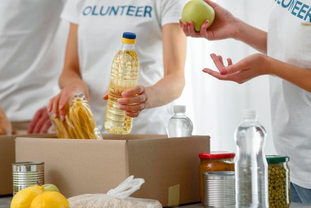 Freiwillige, die kisten mit lebensmittelspenden vorbereiten