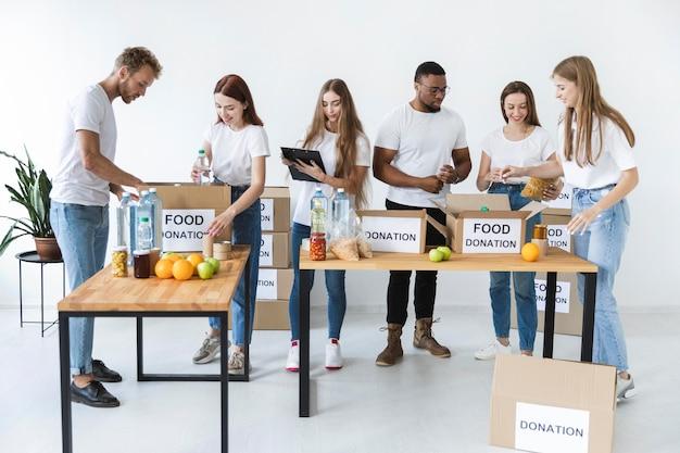 Freiwillige, die kisten mit spendenvorräten vorbereiten