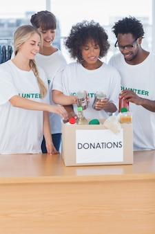 Freiwillige, die lebensmittel in spendenkasten setzen