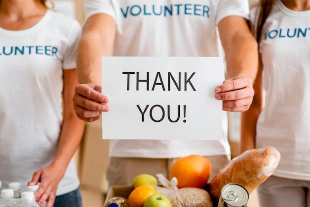 Freiwillige, die sich bei ihnen für die spende von lebensmitteln bedanken