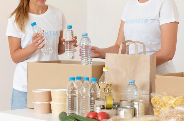 Freiwillige, die wasser für die spende in die tasche stecken