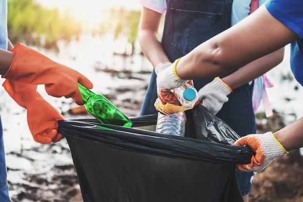 Freiwillige frau, die abfallplastik für das säubern am flusspark aufhebt
