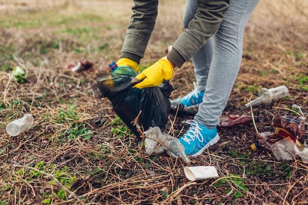 Freiwillige frau, die den abfall im park aufräumt. abfälle im freien einsammeln.