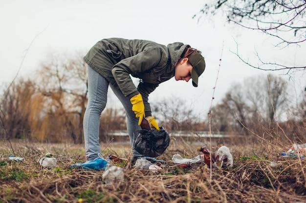 Freiwillige frau, die den abfall im park aufräumt. müll draußen aufheben.