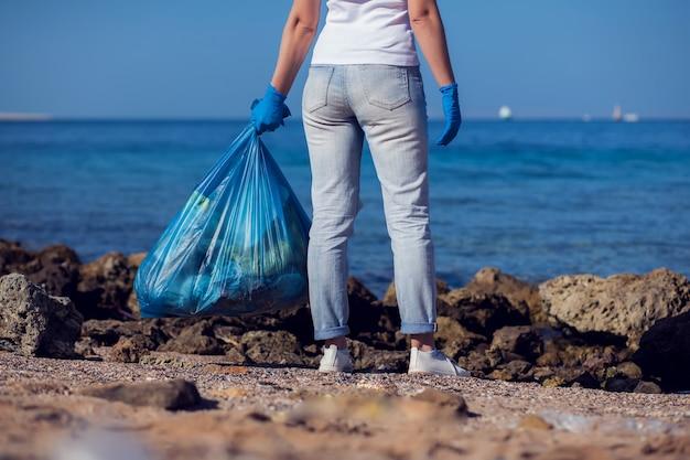 Freiwillige frau mit großer blauer tasche, die müll am strand sammelt. konzept der umweltverschmutzung