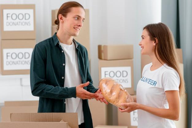 Freiwillige für lebensmittelspende, die brot an bedürftige personen verteilt