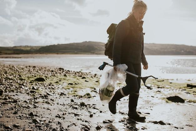 Freiwillige für strandreinigung, die mülltüte für umweltkampagne trägt