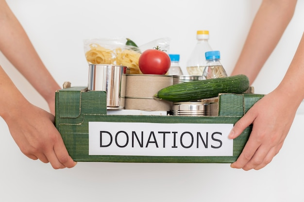 Freiwillige halten kiste mit essen für die spende gefüllt