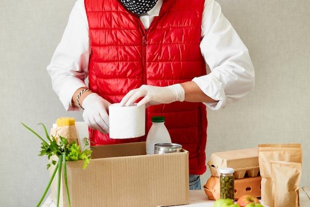 Freiwillige in der medizinischen schutzmaske und handschuhen, die lebensmittel in die spendenbox legen