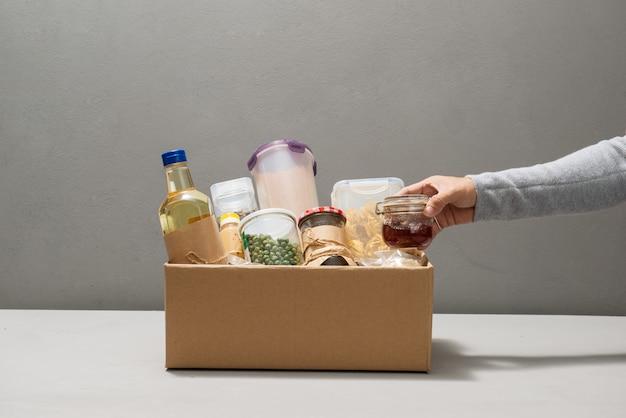 Freiwillige in handschuhen, die lebensmittel in einem spendenkarton mit verschiedenen lebensmitteln halten.