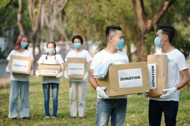 Freiwillige in medizinischen masken tragen kartonschachteln und pakete mit gespendeten klamotten und lebensmitteln für obdachlose