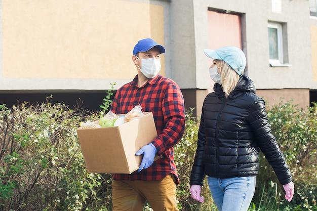 Freiwillige in schutzmasken gehen mit einer schachtel lebensmittel und wohltätigkeit die straße entlang.