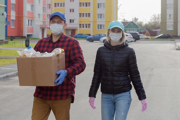 Freiwillige in schutzmasken mit einer schachtel essen gehen die straße entlang