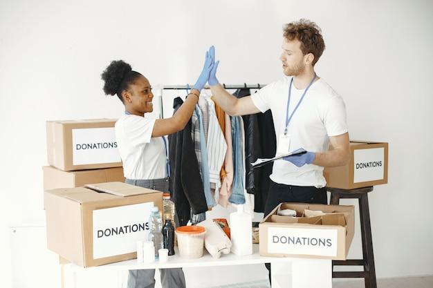 Freiwillige mädchen und männer. freiwillige im verteidigerhandschuh. verpackungsboxen mit.