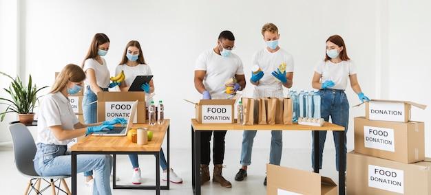 Freiwillige mit medizinischen masken und handschuhen bereiten kisten für die spende vor