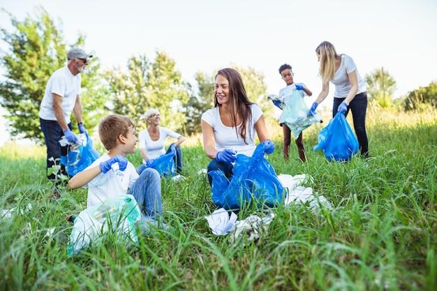 Freiwillige mit müllsäcken, die müll im freien aufräumen - ökologiekonzept.