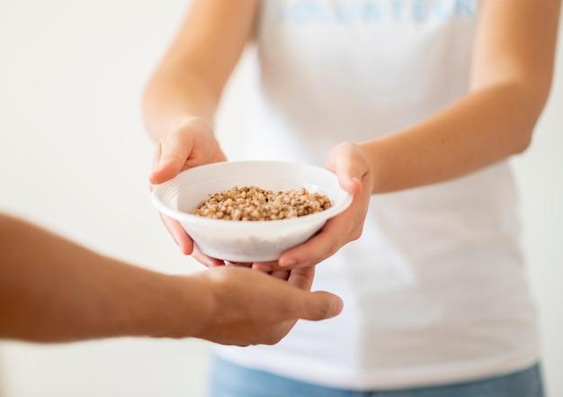 Freiwillige übergabe einer schüssel mit gespendetem essen an eine bedürftige person