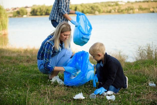 Freiwilligen-, wohltätigkeits-, menschen- und ökologiekonzept, freiwillige, die beim sammeln von müll müllsäcke verwenden.