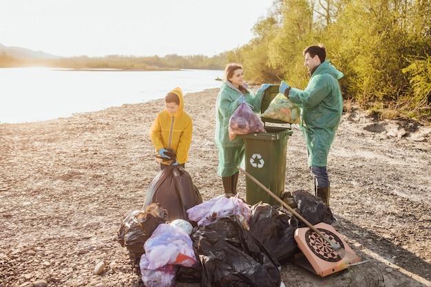 Freiwilligenarbeit, wohltätigkeit, reinigung, menschen und ökologiekonzept. gruppe von glücklichen familienfreiwilligen mit müllsack-reinigungsbereich im park nahe see.