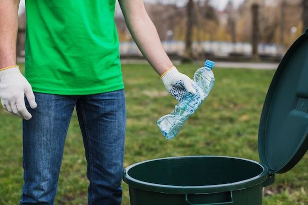 Freiwilliger, der flasche in abfalleimer setzt