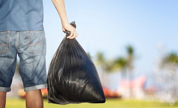 Freiwilliger junger mann, der müll im garten, im kopierraum, im sonnenuntergangslicht, im weltumwelttag sammelt