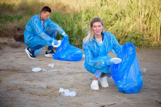 Freiwilliger mann, der müll am strand sammelt. ökologiekonzept.