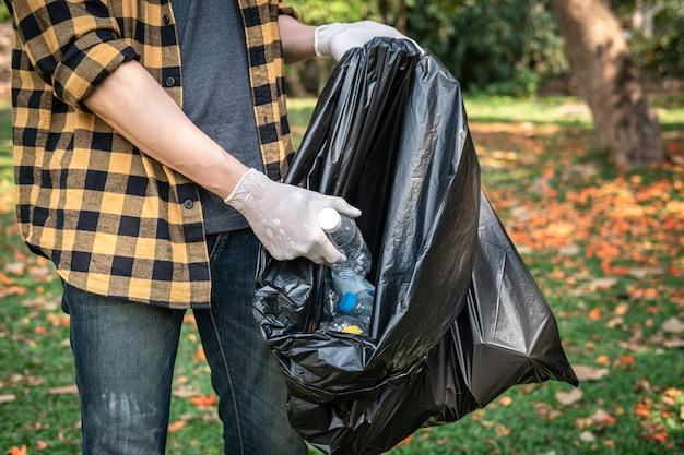 Freiwilliger mann in handschuhen, um plastikflaschen in eine schwarze plastiktüte aufzunehmen, um den park während der umweltaktivitäten zu reinigen, um müll zu sammeln