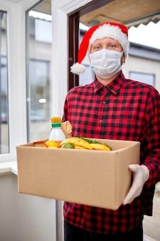 Freiwilliger mann mit weihnachtsmütze und schutzmaske und handschuhen, spendenbox zu hause zu hause, holiday courier mit verpackungsbox mit essen, kontaktlose lieferung,