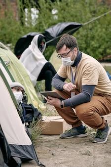 Freiwilliger mit tablet sitzt auf kniebeugen bei einem der flüchtlingszelte