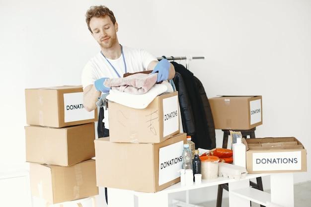 Freiwilliger sammelt dinge von spenden. guy packt kisten mit dingen. der mensch vergleicht die begabung.