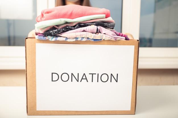 Freiwilliges mädchen mit einer spendenbox mit second-hand-kleidung