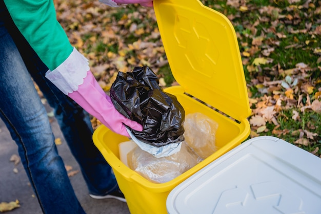 Freiwilliges mädchen sortiert müll in der straße des parks. konzept des recyclings