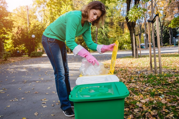 Freiwilliges mädchen sortiert müll in der straße des parks. konzept des recyclings.