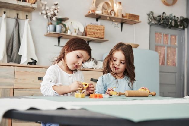 Freizeit, in der die eltern nicht zu hause sind. zwei kinder, die mit den gelben und orange spielwaren in der weißen küche spielen