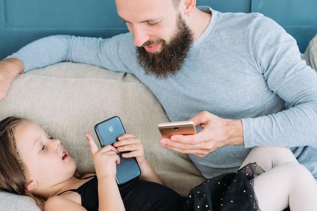 Freizeit in der familie. kommunikation zwischen vater und kind. papa und sein kleines mädchen benutzen das handy und reden. entspannter zeitvertreib zu hause und entspannter lebensstil.