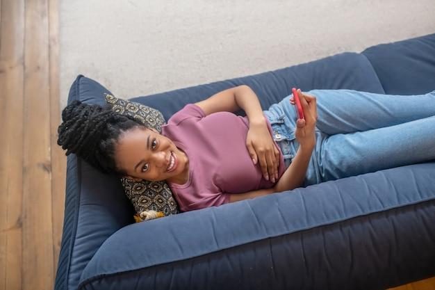 Freizeit. schöne junge dunkelhäutige glückliche frau, die freizeit mit dem smartphone verbringt, das zu hause auf dem sofa liegt lying
