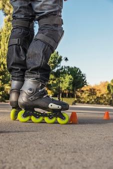 Freizeit-, sport- und menschenkonzept - nahaufnahme der beine beim rollschuhlaufen auf der straße von hinten