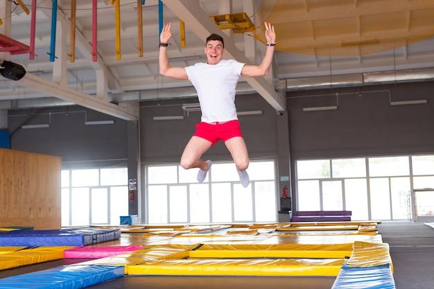 Freizeit, sportspiele und interessen - lustiger junger mann, der im fliegenpark trampoliert.