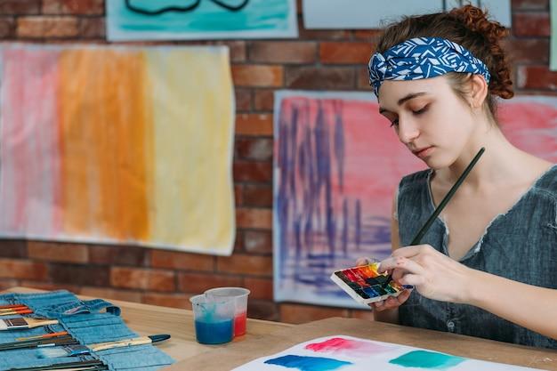 Freizeit und inspiration. junger weiblicher linkshändiger maler, der abstrakte kunstwerke mit aquarell schafft