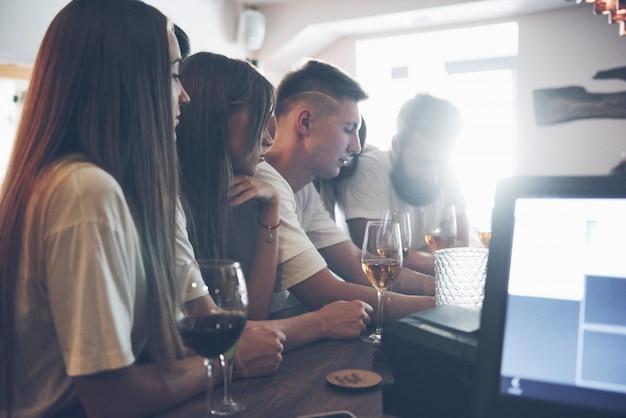 Freizeit- und kommunikationskonzept. gruppe von glücklich lächelnden freunden, die getränke genießen und an der bar oder im pub sprechen