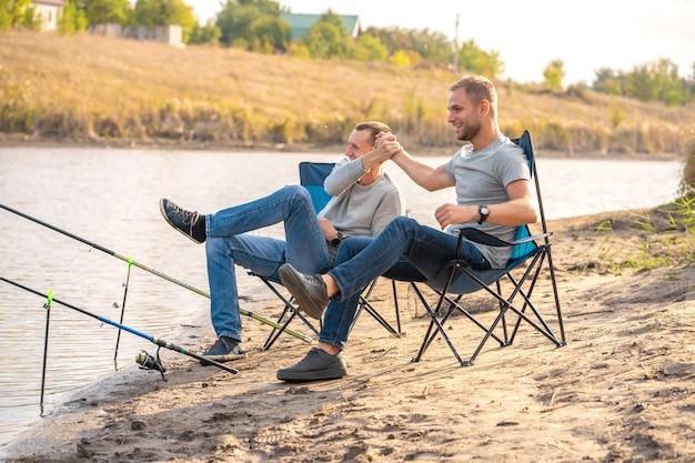 Freizeit- und personenkonzept. glückliche freunde mit angelruten auf pier durch seeufer.