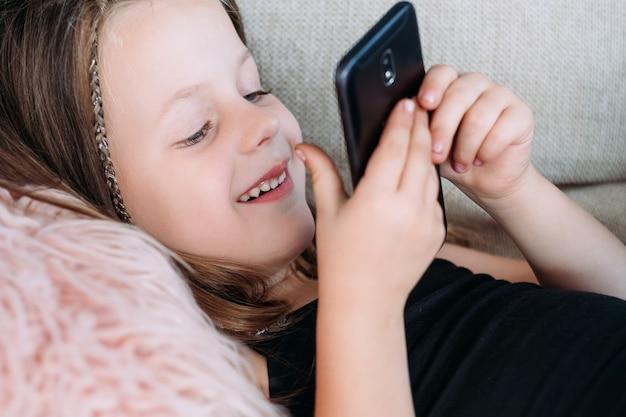 Freizeit und unterhaltung für kinder. technologie und digitale geräte in der kindererziehung. glückliches lächelndes mädchen, das spiele auf dem handy spielt.